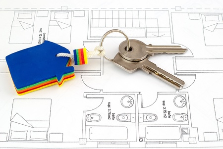 House key on blueprints with an architecture model in the background  photo