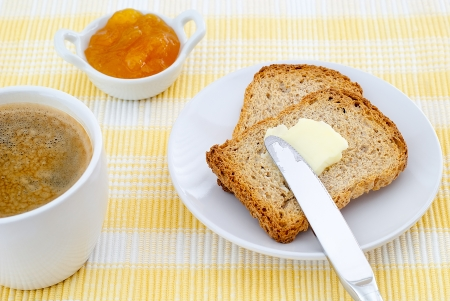 breakfast of toast with butter and jam and coffee on yellow placemat photo