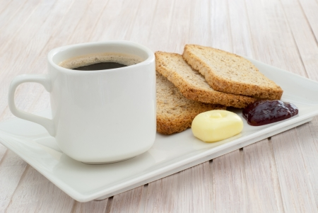 black coffee and toasted with butter and marmalade served in plate on white table photo