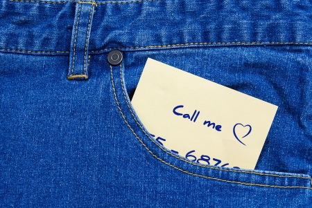 phone number: phone number written on a yellow posit a jeans pocket