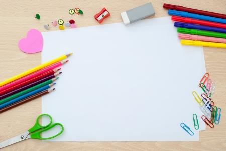 utiles escolares: Los �tiles escolares con papel en blanco en el escritorio de la escuela