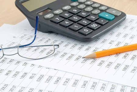 Calculator with pencil and glasses on financial data on the desk photo
