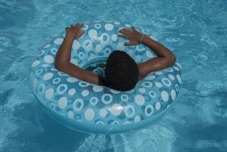 Girl floating in blue swimming tube photo