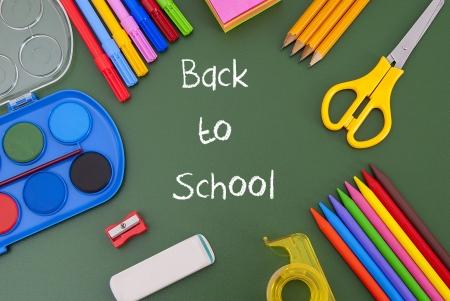utiles escolares: Volver a la escuela por escrito en una pizarra con �tiles escolares