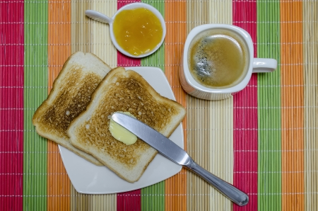 Two slices of french toast with butter and peach jam, and coffee for breakfast photo