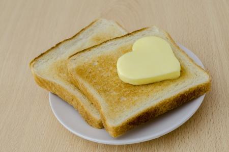 mantequilla: dos rebanadas de pan tostado en un plato blanco con mantequilla en forma de coraz�n