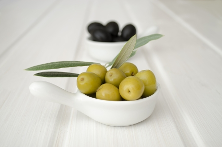 a bowl of green olives in the foreground and the background blurred bowl of black olives on white table photo