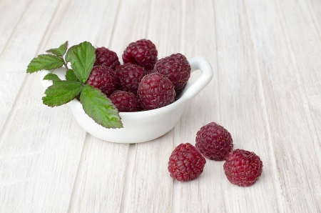 raspberry bowl decorated with green leaves on white wooden table photo
