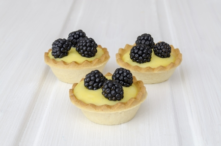 three delicious puff pastry, cream and fresh blackberries on white wooden table photo
