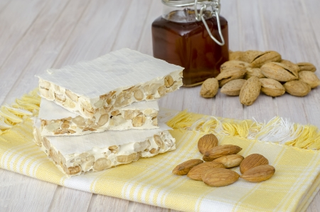 Pieces of Christmas hard almond turron on white background  This traditional dessert is very popular in Spain  in Christmas time Фото со стока