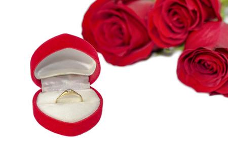 roses rouges: anneau de diamant dans la bo�te sur la forme de coeur rouge avec des roses rouges Banque d'images