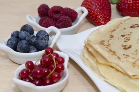 accompanied: plate with stack of pancakes accompanied with bowls of different fruits