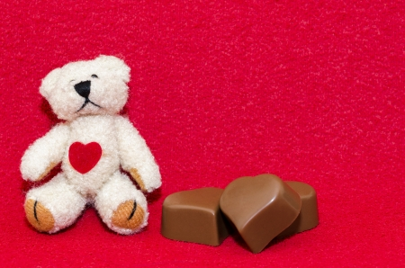 valentine s day teddy bear: Teddy bear with three heart shaped chocolates on a red background