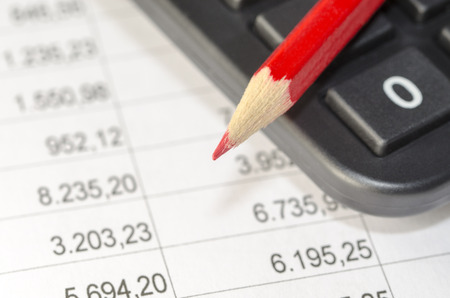 taking charge: calculator and red pen on the background of financial balance sheets Stock Photo