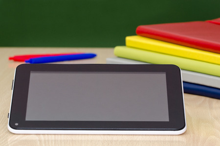 digital tablet leaning against a colorful notebooks,on a school desk  photo