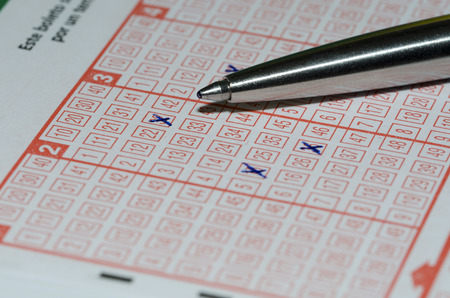 petticoat: Using a pen to fill out a lottery slip to play the lotto