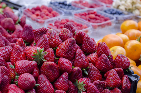 Closeup of strawberries and other fruits exposed to be sold on the market photo