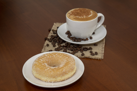 donut and coffee capuccino on brown wooden table of a coffee shop