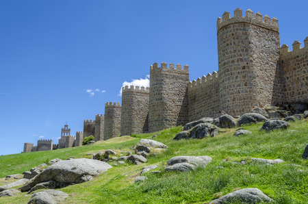 The wall of Avila, Spain. The stone wall with its turrets behind a green lawn