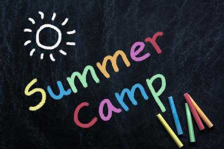 summer camp text and sun drawing on black chalkborad Archivio Fotografico - 104704504