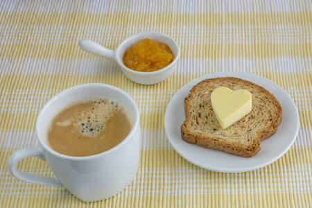 breakfast of coffee and an integral toast with butter and melotocon jam on a yellow checkered tablecloth Imagens