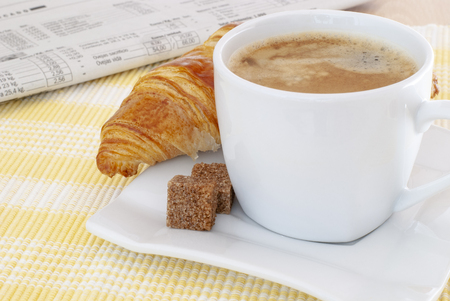 close-up of coffee and brown sugar cubes with croissant and newspaper in the background