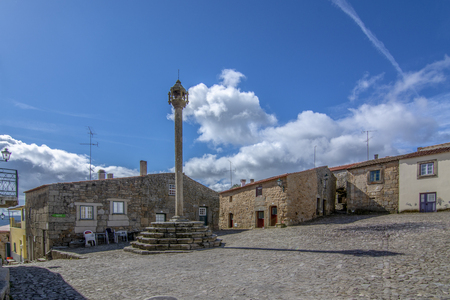 View of the central square of the historic village of Castelo Mendo, in Portugal, with a church and pillory Фото со стока
