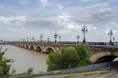 Panorama of Pont de pierre, old stony bridge in Bordeaux in a beautiful summer day, France Фото со стока