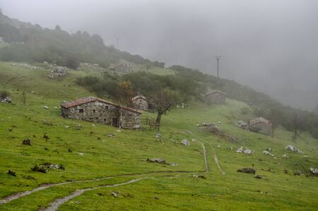 typical stone cabins at foggy day of the mountain at Ria?o, Spain Stock fotó