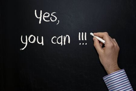 A hand writing 'YES! You Can' on chalkboard.