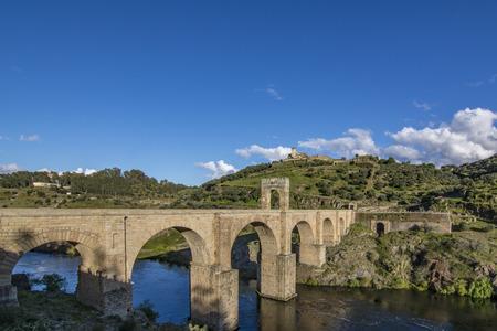 The stone Alacantara Bridge is an two thousand years old roman bridge that crosses the Tagus River. Stock Photo
