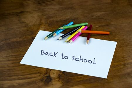Desk with stationary and Back to school sign. Studio shot on wooden background.