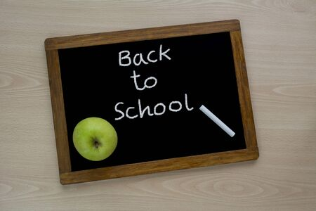 Back to school, the inscription on the mini-Board, the layout of the Board and chalk on the desk , with green apple. the concept of preparation for school.