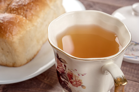 Cup of tea, white bread in glass plate, butter dish and on wooden table Stock Photo