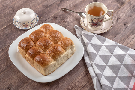 White bread in glass plate, spoon, napkin, butter dish and cup of tea on wooden table