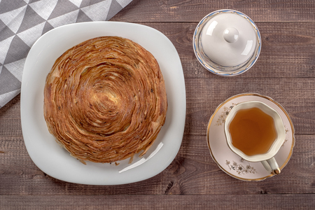 Sweet cinnamon bun roll swirl in glass plate, napkin, butter dish and cup of tea on wooden table Stock Photo