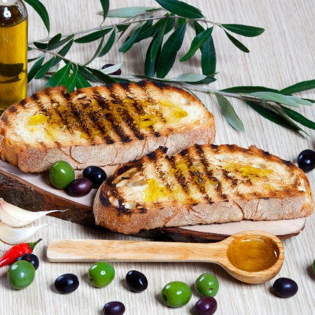 Italian bruschetta, olives and a wooden spoon photo