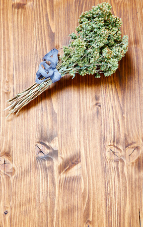 Oregano on a wooden table with copy space photo