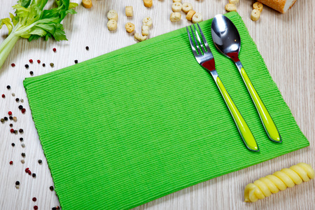 a green napkin with flatware on a table