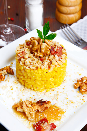 speck: risotto with walnuts, saffron, speck on a dish Stock Photo