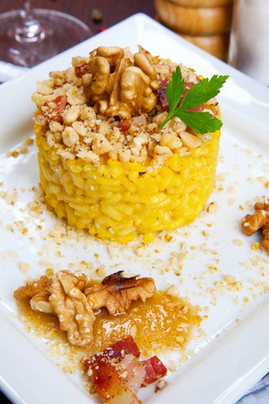 risotto with walnuts, saffron, speck on a dish Stock Photo