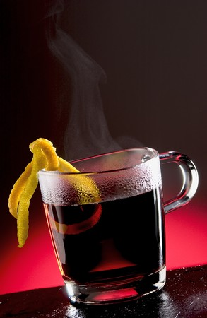 soporific: Hot Tea Punch with steam and sliced lemons Stock Photo