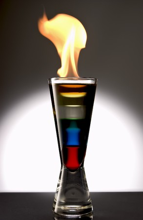 pellucid: Pousse Café with red, blue, green, white, yellow and orange layer with a small flame