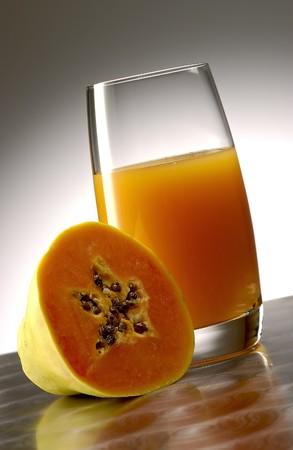 pellucid: Papaya juice with half papaya on polished aluminum surface.