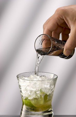 caipirinha: Second step caipirinha making, pour in sugarcane booze.