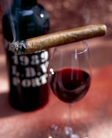 elixir: Cigar situada encima de un vaso de vino tinto, bottel en la espalda.  Foto de archivo