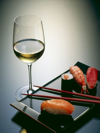 asian flavors: Sushi with chopsticks and a glass of wine. Stock Photo