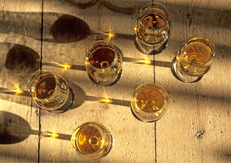 soporific: six glasses of cognac standing on a table of wood