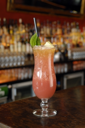 pellucid: Zombie Punch with mint leave black straw in a bar setting.