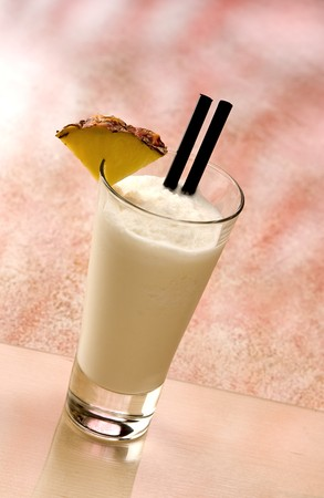 Linda Pina Colada Cocktail with a piece of pineapple and two black straws photo